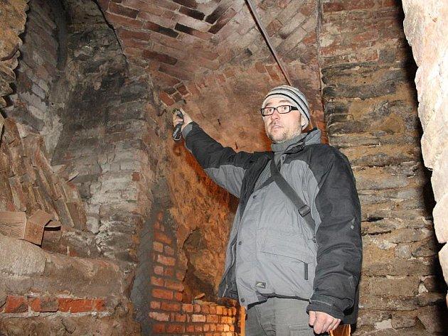 Archeolog Marek Peška ze společnosti Archaia ukazuje v jednom ze sklepů pod jihlavskou základní uměleckou školou zazděný gotický portál. V pozadí je vidět také práce současných zedníků. Sklepy v budově umělecké školy připomínají labyrint.
