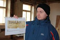 Historik Radim Gonda ukazuje kopii jednoho z fragmentů, kterou zedníci v budově objevili.