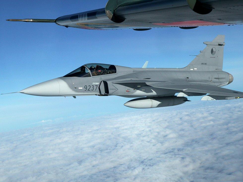 Pilot vede stroj s výsostnými znaky České republiky nad Švédskem blízko polárního kruhu. Nad gripenem let sleduje posádka cvičného švédského letadla SK60.