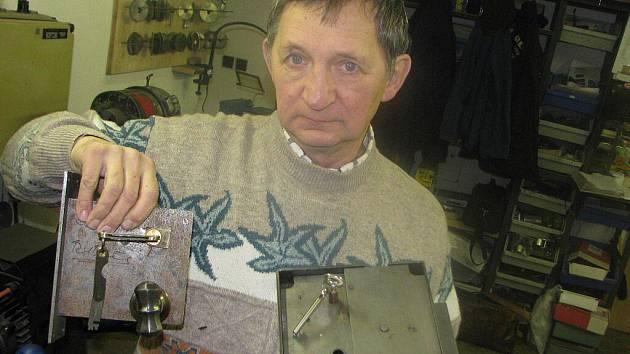 Josef Jakubík ukazuje trezorové zámky ve staré asi 150 let, lišící se druhem klíčů. Vlevo je zámek s klasickým píchacím nožovým klíčem. Zámek vpravo má standardní jednostranný dozický klíč s otvorem. Používají se stále ve starých trezorech.