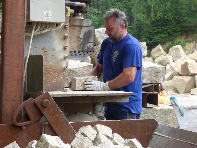 U stroje na výrobu kostek stojí zaměstnanec lomu pět až šest hodin denně. Jednou nohou při tom sešlapává pedál.