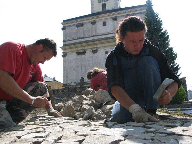 Hory větších kamenů spotřebují dlaždiči na nové chodníky. Malý kolový nakladač stále naváží další hromady kamení, které se záhy promění v trochu kostrbatou plochu. Ve středověku se jinak nedláždilo.