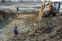 Bagry se zaryly do několikametrové vrstvy mazlavé hmoty. Co najdou na dně Staroměstského rybníka v Telči archeologové? Doufají, že toho bude spousta. Ilustrační foto.