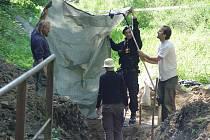 Kostry, které minulý týden odkryli archeologové u Dobronína, pečlivě zdokumentovali, než  je vyzdvihli ze země. Kvůli dobrému světlu bylo nutné při focení použít improvizovanou clonu.