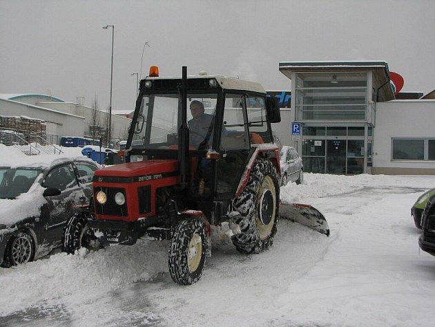 Služby města Jihlavy uklízejí nejdřív rušná místa. Na snímku je traktor, nasazený u obchodního centra při ulici Romana Havelky, čistí parkoviště před Vodním Rájem.