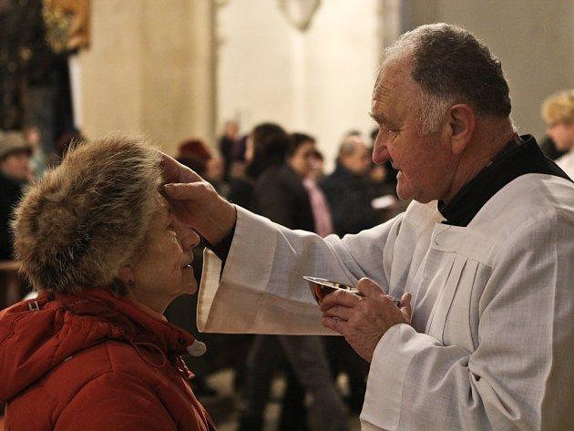 Na snímku přijímá věřící od pomocníka kněze Jiřího Noska (vpravo) na čelo takzvaný popelec při ranní bohoslužbě v chrámu svatého Jakuba.