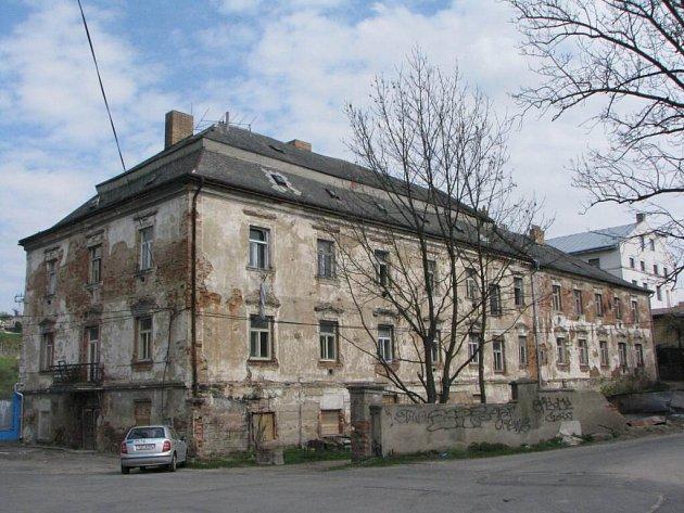 Objekt v Mlýnské ulici je v havarijním stavu. Na opravu střechy, fasády, společných prostor a společných rozvodů nemá majitel objektu už energii. Dům chce prodat. Zájemcem je výrobce oken a dveří, sousední firma Plastikov.