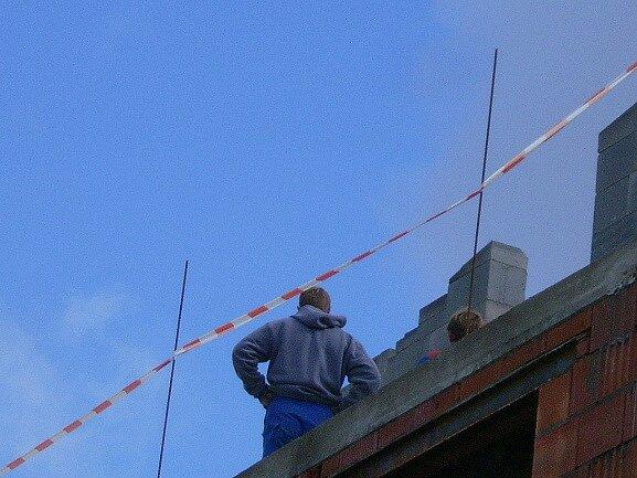 Zedník pohybující se ve výšce na kraji rozestavěného domu, riskuje. V případě kolize by ho páska, která má nahrazovat zábradlí, nezachránila.