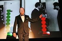 Moderátor Eduard Hrubeš  na jevišti kina Dukla vysvětluje na barevné grafice, jaké pokračování filmu si diváci vybrali. Tentokrát zvítězila varianta,  že spoře přioděnou sousedku pozve  Horníček do  bytu, přestože každou chvíli čeká manželku.
