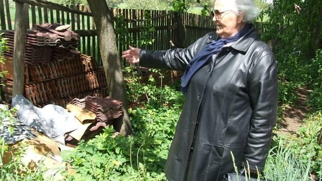Půda je kontaminovaná. Marie Šebestová ukazuje na nepořádek na své části pozemku. Podle jejích slov odpad půdu ničí.