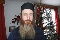 Kněz Vladimír Jeremiáš Cvak v teple domova před ozdobeným vánočním stromkem.