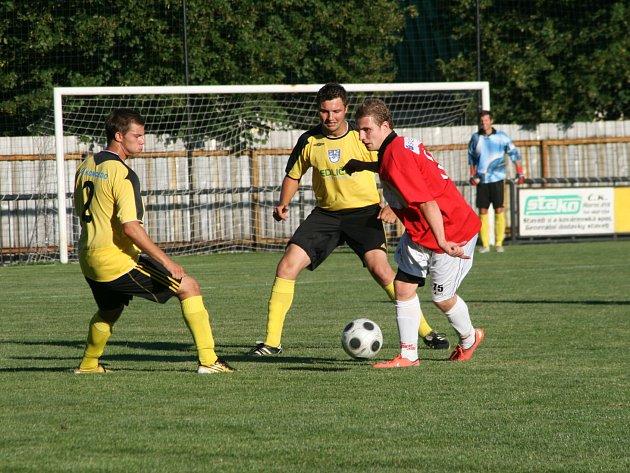 Červenokostelecký Tomáš Martínek (u míče) v obležení hráčů Kratonoh.