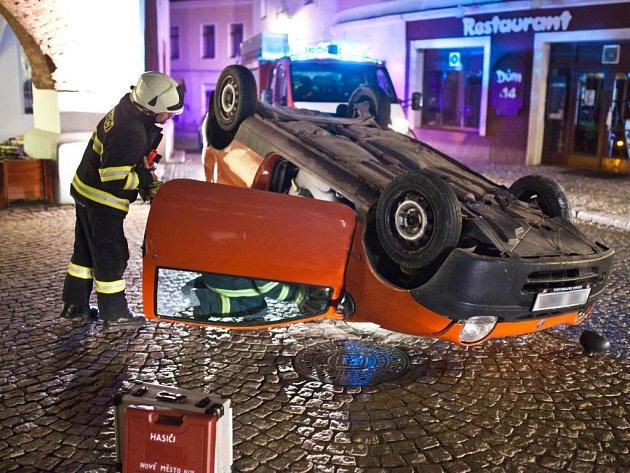 Nehoda na novoměstském náměstí, kde automobil narazil do pilíře domu v úzké části silnice a převrátil se na střechu.