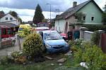 Modrý Opel nedobrovolně zaparkoval na zahrádce rodinného domu.