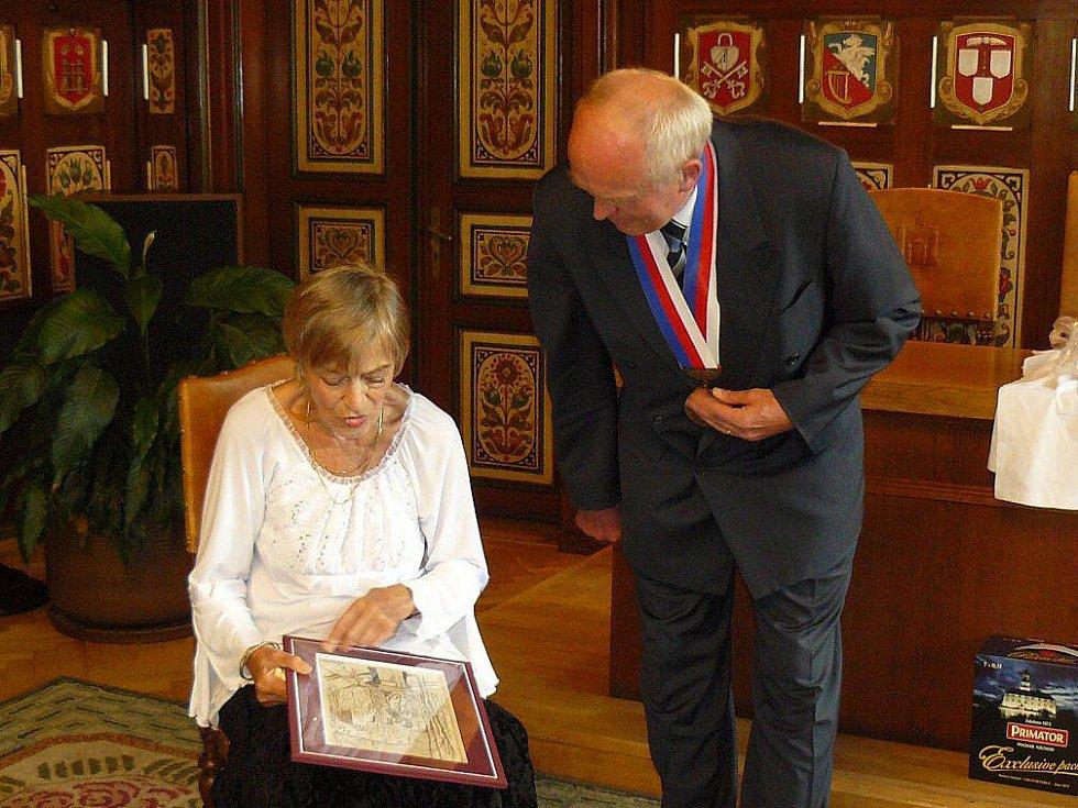 Ljuba Skořepová dostala jako dar obraz náchodského malíře Oldřicha Šafáře. Vpravo místostarosta Náchoda Jaroslav Rohulán.