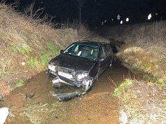 Řidička Fabie nezvládla průjezd pravotočivou zatáčkou a skončila mimo silnici v potoce.
