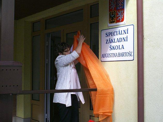 Jana Hartmanová, ředitelka Speciální školy Augustina Bartoše v Červeném Kostelci, odhaluje desku se jménem tohoto pedagoga.