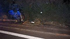 Vozidlo skončilo v blátě na boku u plotu zahrady.