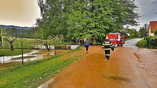 Rozvodněný potok v Křinicích ohrožoval rodinný dům. Hasiči ze Stanice Broumov, JSDH Broumov a JSDH Křinice stavěli zábrany z pytlů s pískem a dřevěných podlážek.