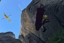 Lezec spadl z několikametrové výšky, naštěstí byl při vědomí a se záchranáři komunikoval. Zraněný byl ve vakuové matraci v podvěsu pod vrtulníkem vynesen z těžko přístupného terénu. Foto: HZS KHK