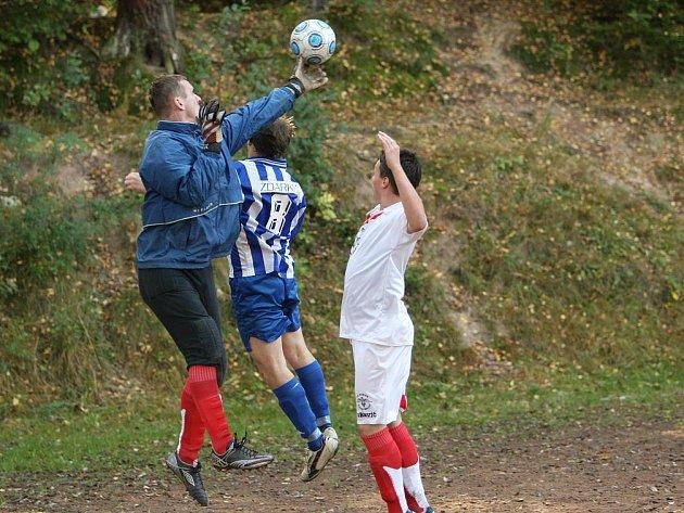 Brankář Velkého Dřevíče Michal Lokvenc si stahuje míč do své moci před dotírajícím hráčem Žďárek B (v pruhovaném).