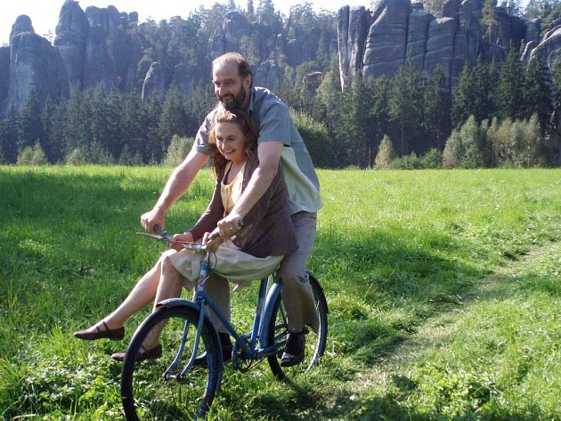 Hlavní  protagonisté filmu Eva Holubová a Jaromír Dulava na kole s pozadím skal.