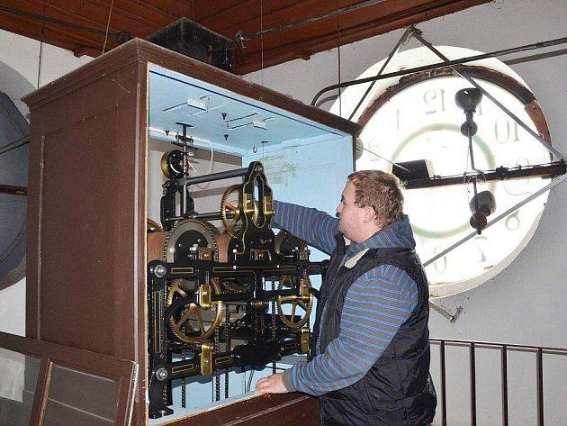 TOMÁŠ UNGER kontroluje hodinový stroj.