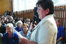 Marie Petruželková, předsedkyně Rady rodičů, čte petici za odvolání ředitele Františka Netušila. Na jednání v  sokolovně v Krčíně s ní souhlasily stovky lidí.