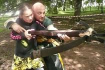 Člen skupiny historického šermu Manové Přemysla Otakara učí jednu z malých návštěvnic slavností střílet z kuše.