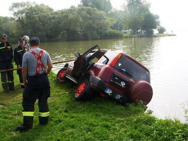 Řidič červené Hondy chtěl vycouvat, ale místo toho se rozjel dopředu, přímo k vodní hladině. Ještě však stihl zatočit, takž nevjel do vody přímo, ale dvěma koly zůstal na trávě.