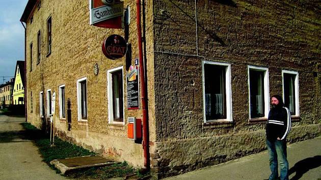 """Stanislav Pitaš na snímku stojí před kulturním domem, kde je na jedné straně pohostinství, jež provozuje, a na straně druhé myslivecká klubovna Nora. """"Ta funguje jako nálevna, a ne jako klubovna,""""  nepochybuje  místostarosta."""