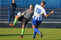 BRANKÁŘ Slatiňan odkopává míč v sobotním divizním zápase před náchodským Jakubem Vaněčkem, který gólmana soupeře přece jen jednou pokořil.