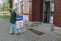 Dovoleno. člen volební komise v Bezděkově Jaroslav Podávka uklízí tabuli navigující voliče.