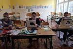 Učitelky usedají do školních lavic a šijí roušky