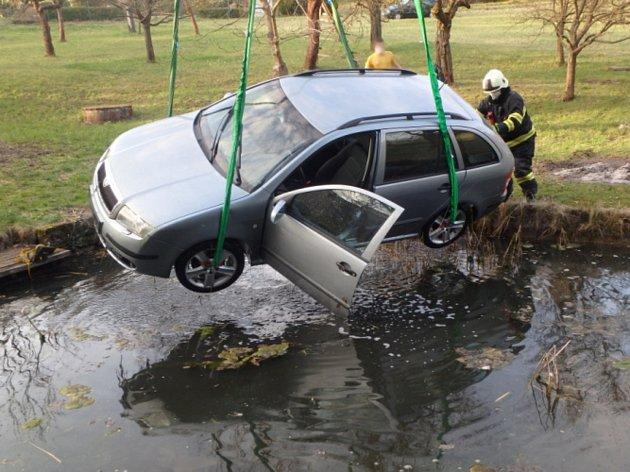 Osobní vozidlo, které sjelo do požární nádrže, vyprošťovali včásti Horní Kostelec profesionální hasiči zNáchoda.