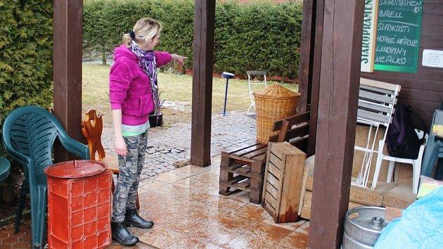 LADA KŘÍŽOVÁ s pomocníky uklízí následky havárie vodovodního potrubí. Prasklo zhruba 130 metrů od Dřevěnky a valící se voda si to zamířila přímo do výčepu.