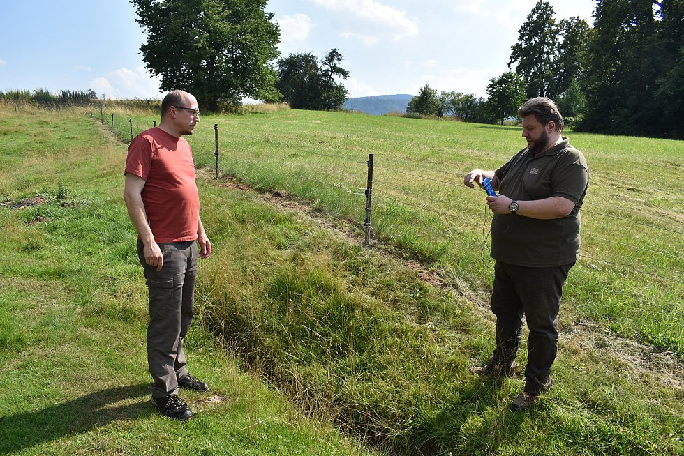 Kamil Zahradník z Lesnicko dřevařského vzdělávacího institutu pomocí zkoušečky předvádí, že ohrada pro ovce je pod ochranou elektrického ohradníku.