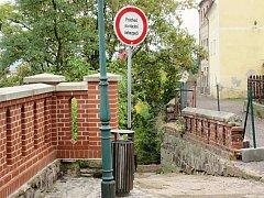 NOVÁ A STARÁ. Cihlová zeď v ulici Na Hradbách má dvě tváře. Ta opravená je bezpečná, což se o té staré říct nedá. Důkazem je nedávné zborcení části zdi (v horním výřezu). Vzniklá díra je teď provizorně ochráněné pletivem.