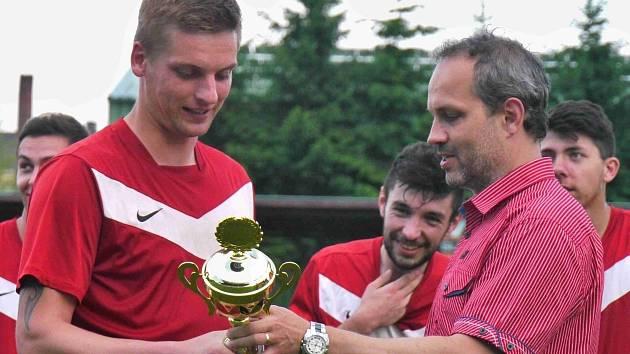 Předseda VV OFS Náchod Petr Vítek (vpravo) předává fotbalistům jaroměřské rezervy pohár za vítězství v letošním ročníku Jopeco okresního přeboru mužů.