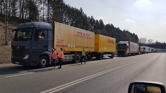 Řidiči kamionů v koloně dostávají jídlo a pití.