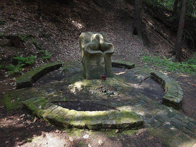 """Přímo na místě tragédie v malém lesním lomu vyrůstá z chodníku ve tvaru kříže a kruhu """"stéla"""", připomínající kříž i květinu."""