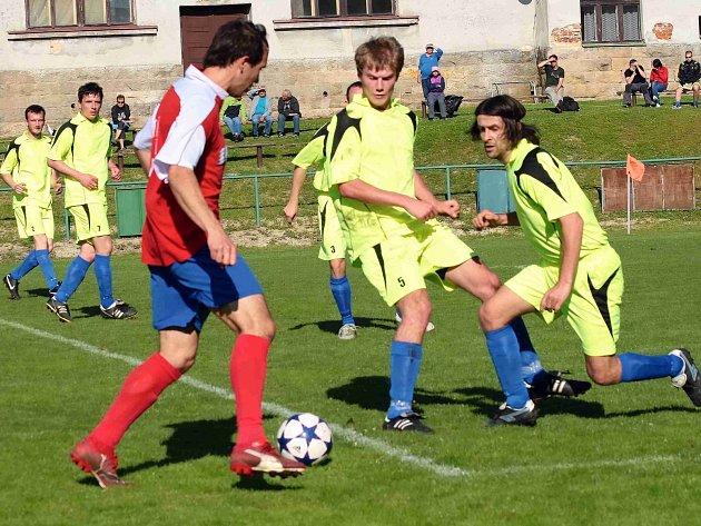 NOVOMĚSTSKÝ stoper Pavel Zákravský (v červeném) se snaží najít skulinku v přesile hráčů Miletína.