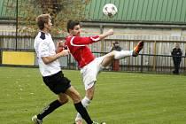 ČERVENOKOSTELECKÝ kapitán Michal Gross (v červeném) odvrací míč před dotírajícím hráčem Rychnova nad Kněžnou.