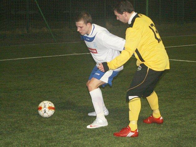 Domácí Tomáš Martínek si kryje míč před dotírajícím trutnovským protihráčem.