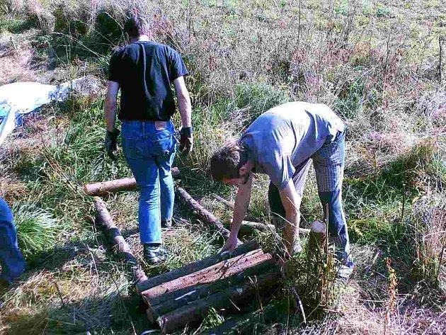 Členové neformálního seskupení subterén stavějí novou dřevěnou lávku, která má zpřístupnit nedávno opravený smírčí kříž.