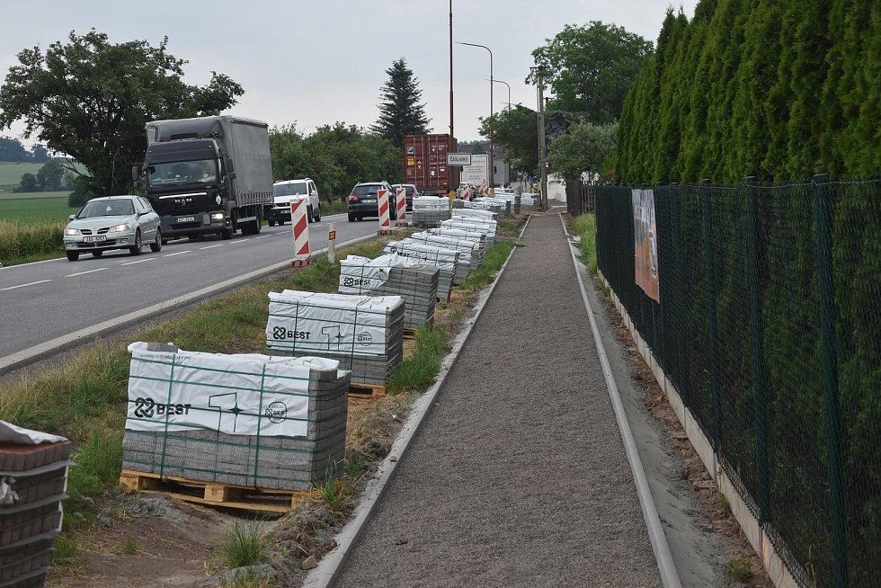 Vedle frekventované silnice se buduje potřebný chodník.