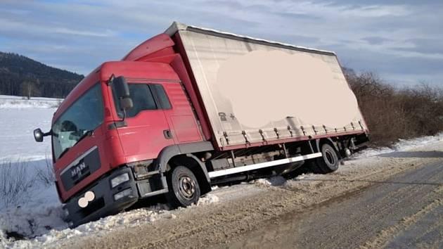 Zapadlému nákladnímu automobilu hrozilo převrácení. Pomocí vyprošťovacího automobilu se vůz podařilo hasičům vytáhnout zpět na silnici.