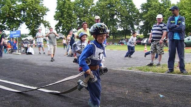 Aleš Bednář z  SDH Malé Svatoňovice běží s hadicemi k rozdělovači na nedělních závodech čtvrtého ročníku Stolínské šedesátky. S číslem 38 Vojtěch Matěj z SDH Hajnice.