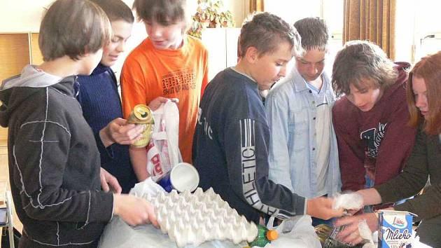 Žáci  se probírají odpady, které si přinesli do školy na včerejší tématické vyučování z domova.