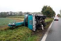 Nákladní automobil s jeřábem, který zde v sobotu po deváté hodině skončil převrácený na bok v příkopu.